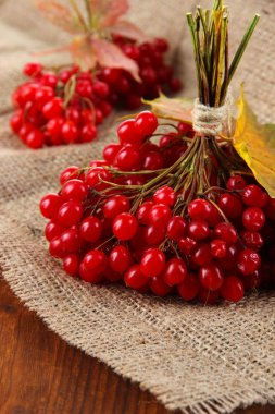 Red berries of viburnum on sackcloth napkin, on wooden background