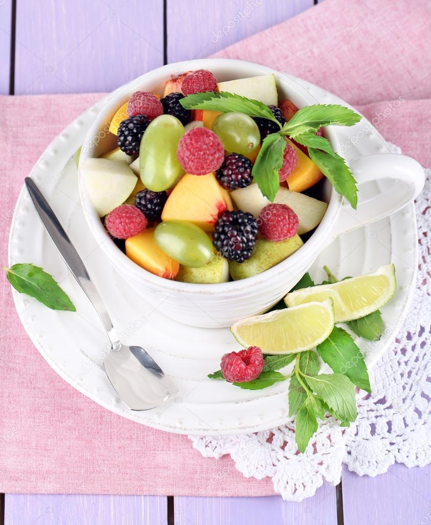 Fruit salad in cup on napkin on wooden table