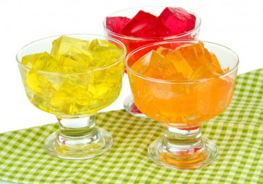 Tasty jelly cubes in bowls on table