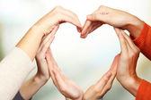 Menschenhände in Herzform auf hellem Hintergrund