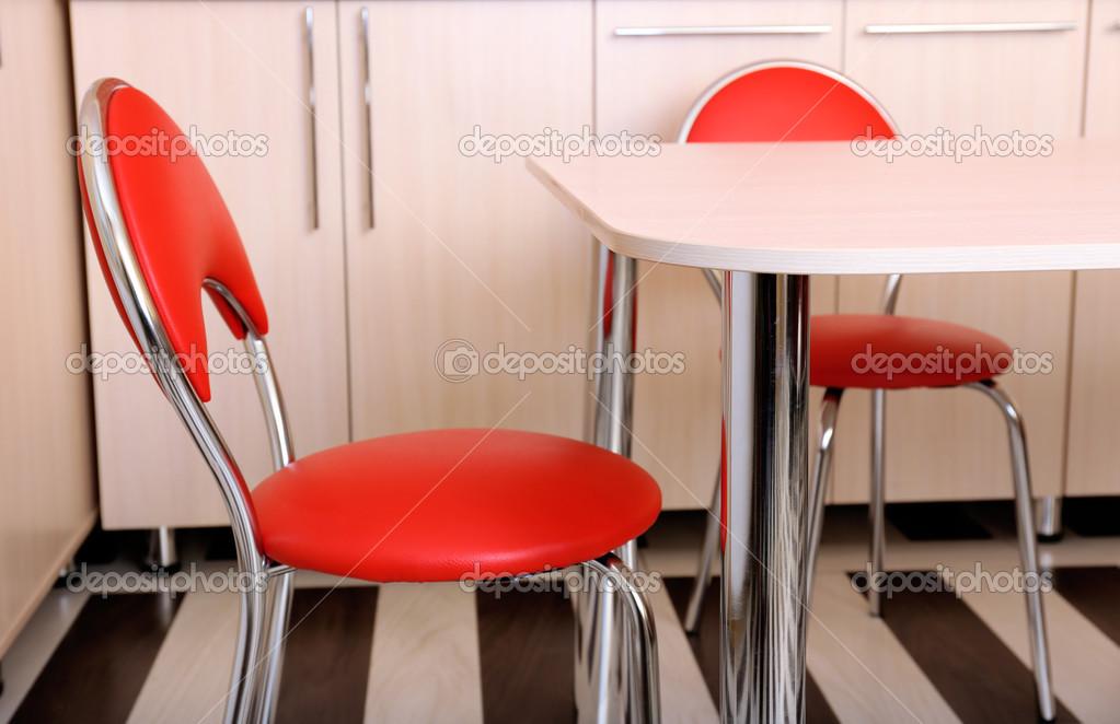 Modernas sillas rojas junto a la mesa en la cocina foto for Sillas de cocina rojas
