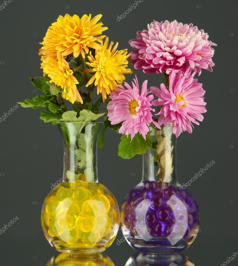 Beautiful flowers in vases with hydrogel on table on gray background beautiful flowers in vases with hydrogel on table on gray background photo by belchonock izmirmasajfo