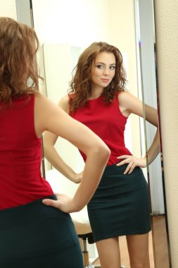 Beautiful girl trying dress near mirror in room