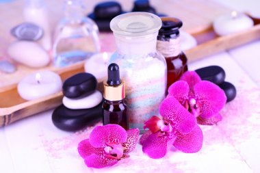 Beautiful spa setting with orchid on white wooden table close-up