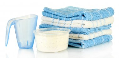 measuring cups with washing powder and towels, isolated on white