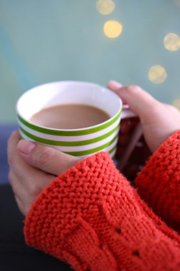 Hands holding mug of hot drink