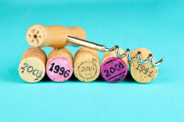 Wine corks with corkscrew on wooden table close-up