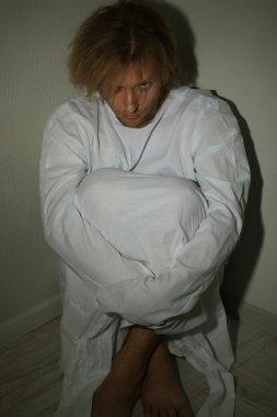 Mentally ill man in strait-jacket
