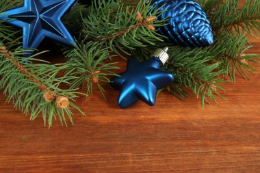 Beautiful Christmas decorations on fir tree on wooden background