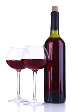 Wineglasses with red wine, grape and bottle isolated on white