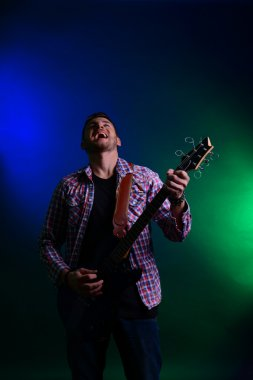 Young musician playing guitar and singing, on dark color background
