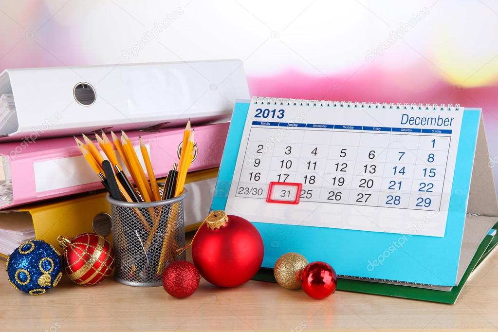 Table with office supplies, calendar and Christmas tinsel close-up