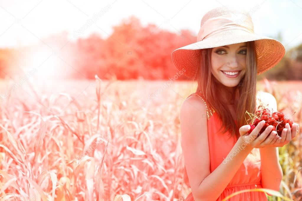 Portrait of beautiful young woman with berries in the field
