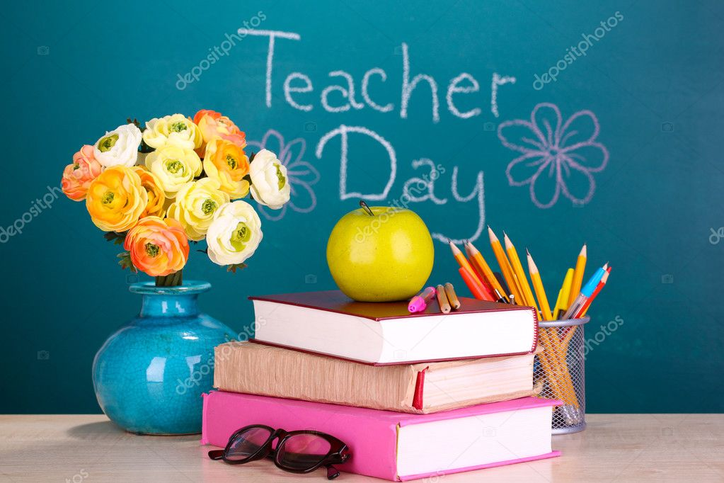 School supplies and flowers on blackboard background with inscription Teacher Day