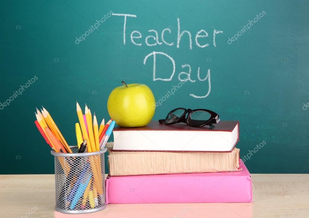 School supplies on blackboard background with inscription Teacher Day