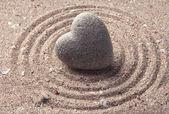 Šedá zen kámen ve tvaru srdce, na písku pozadí