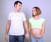 Těhotná žena se svým manželem, drželi se za ruce na šedém pozadí
