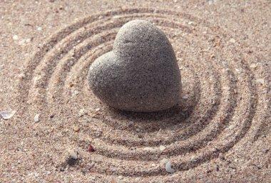 Grey zen stone in shape of heart, on sand background