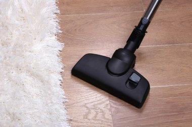 Vacuuming carpet in house