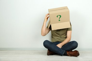 Man with cardboard box on his head sitting on floor near wall