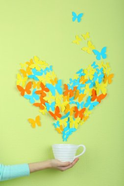 Paper butterflies fly out of cup on green wall background stock vector