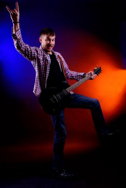 Young musician playing guitar on dark color background