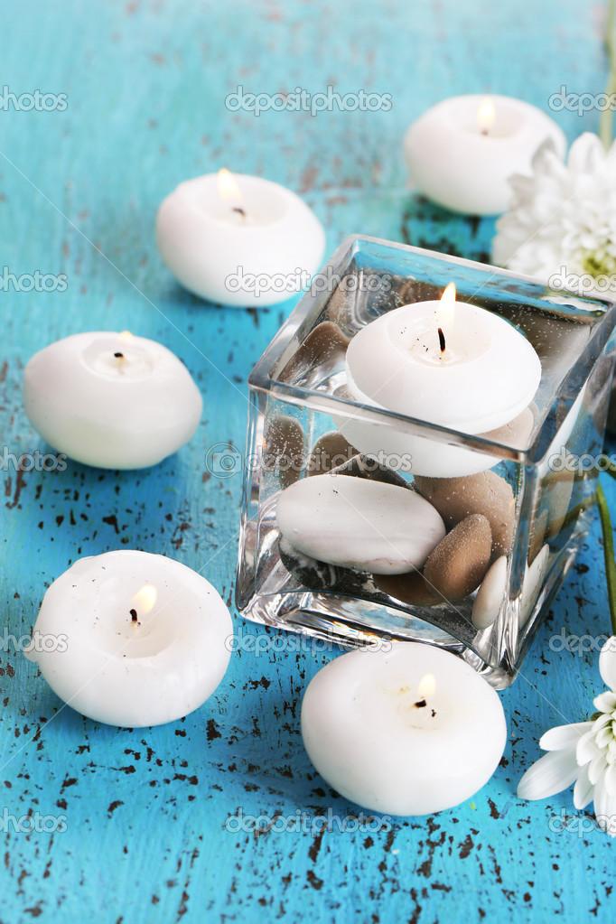 florero decorativo con velas agua y piedras en primer plano de la mesa de madera