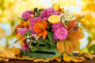 Flowers composition in crate with yellow leaves on table on bright background