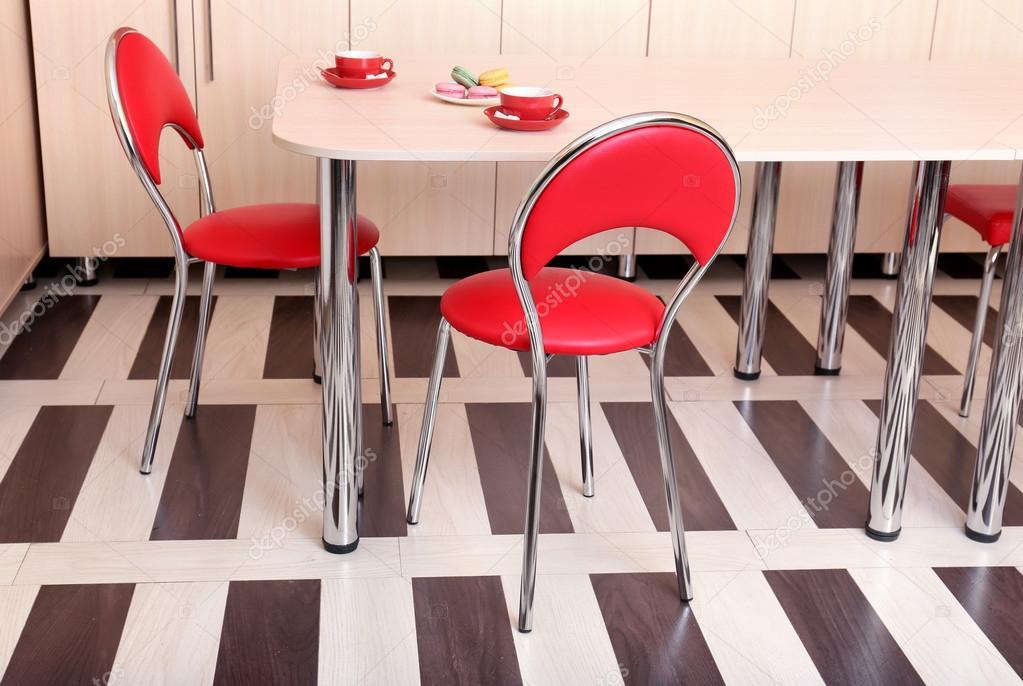 Moderne rode stoelen in de buurt van tafel in keuken u stockfoto