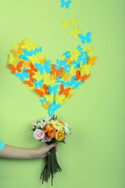 Paper butterflies fly out of flowers on green wall background