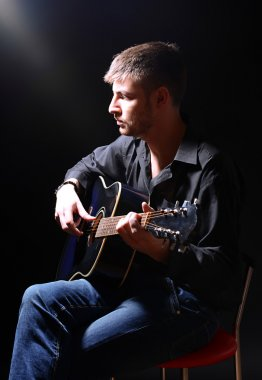 Young musician playing acoustic guitar and singing, on dark background