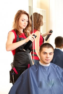 Beautiful girl hairdresser do hairstyle guy in beauty salon