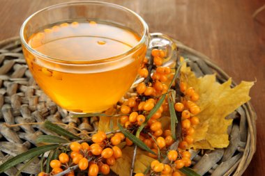 Branches of sea buckthorn with jam on wicker stand on wooden background