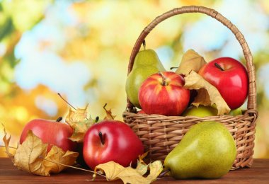 Beautiful ripe apples and pears with yellow leaves in basket on table on bright background