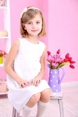 Little girl sitting on small ladder with flowers on pink background