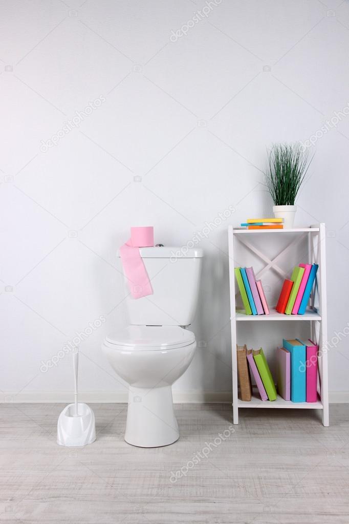 Inodoro blanco y stand con libros, sobre fondo de pared color ...