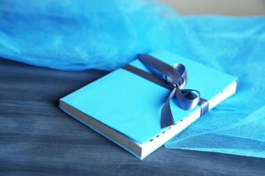 Book wrapped with color ribbon, on wooden table on dark background