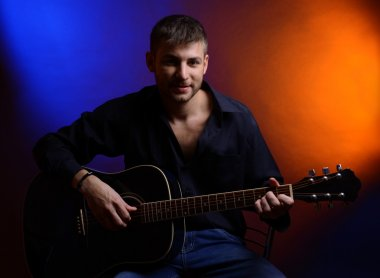 Young musician playing acoustic guitar and singing, on dark color background