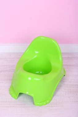 Green potty on floor, on wall background