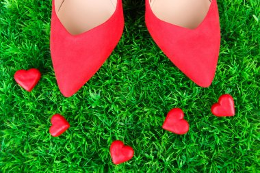 Beautiful red female shoes, on green grass background
