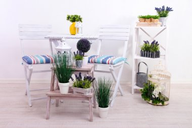 Garden chairs and table with flowers on wooden stands on white background