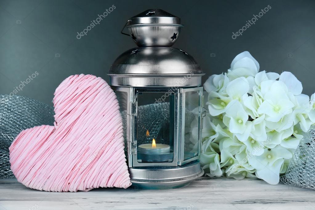 Decorative metallic lantern on wooden table on grey background