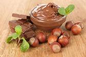 Fotografie süße Schokolade Haselnuss setzte sich mit ganzen Nüssen und Minze auf hölzernen Hintergrund