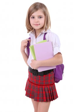 Beautiful little girl with backpack holding books isolated on white