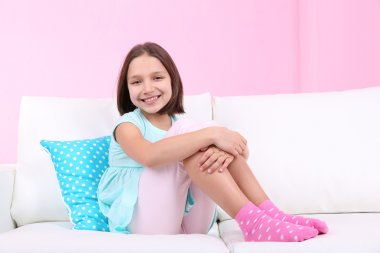 Beautiful little girl sitting on sofa, on home interior background