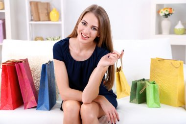 Beautiful young girl  sitting on sofa with shopping bags on home interior background
