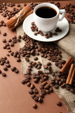 Coffee beans and cup of coffee on table close-up