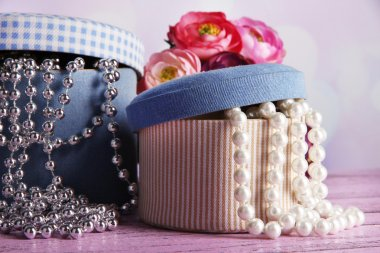 Decorative boxes with beads and flowers on table on bright background