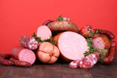 Lot of different sausages on wooden table on red background