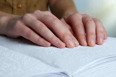 Blind woman read book written in Braille